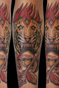 neotraditional flaming three eyed tiger biting skull and bones