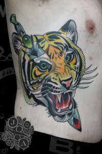 large tiger head on side of body pierced with knife neo traditional by justin acca